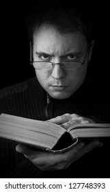 man with book looking at camera, studying black and white portrait