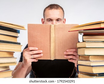 The man is a book lover. Love of reading. A man with an open book next to a stack of books. Bibliophile. A man reading on a white background.