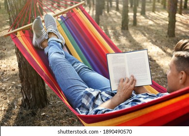 Man with book relaxing in hammock outdoors on summer day