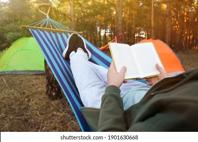 Man with book resting in comfortable hammock outdoors, closeup