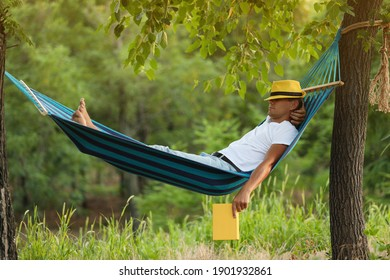 Man with book resting in comfortable hammock at green garden