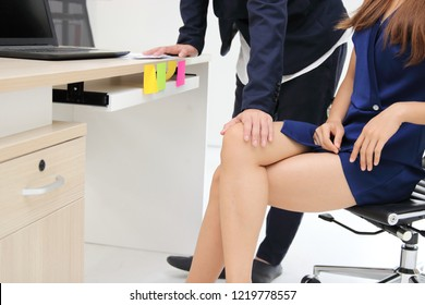 Man boss touching woman knee in workplace of office. Sexual harassment in office
