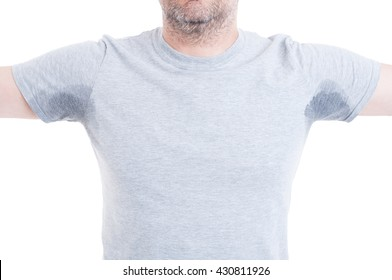 Man with both arms raised and excessive sweat stains on grey t-shirt isolated on white as hyperhidrosis concept