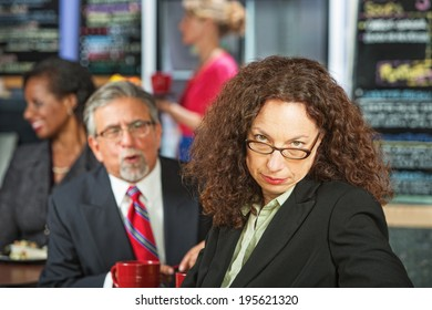 Man bothering frustrated business woman in coffee house