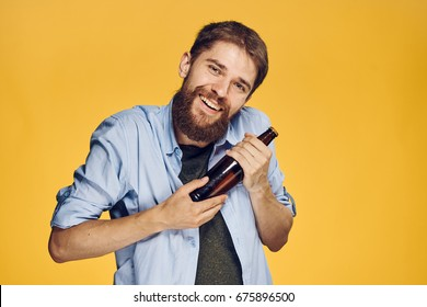 Man with a bottle of beer on a yellow background
