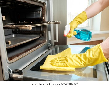 Man with bottle of spray and rag cleaning oven at home kitchen. Housework and housekeeping concept