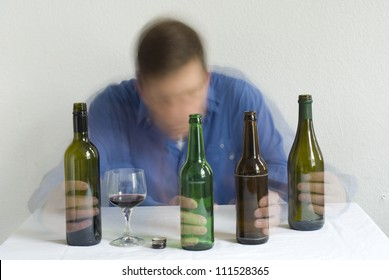 Man with bottles on the table. Blurry movement.