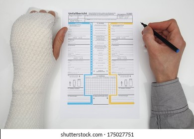 Man with bound hand fills out a accident report