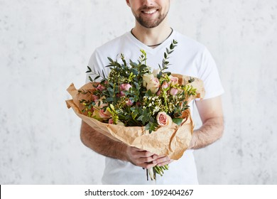 Man with a bouquet of roses. Smiling bearded young man with flowers