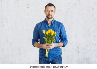 Man with a bouquet of yellow tulips. Yellow tulips in the hands of a bearded man