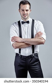 Man with bow tie and suspenders crossing his arms isolated over grey