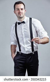 Man with bow tie and suspenders snapping fingers isolated over grey