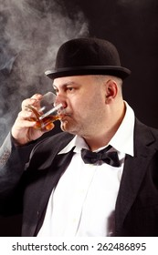 man with a bowler hat and bow tie drink whiskey