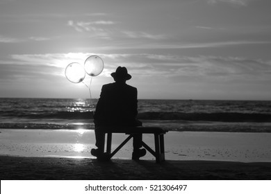 man in a bowler hat on the beach holding two balloons, symbolic surrealistic image about dreams, loneliness and hope