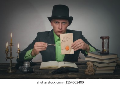 Man in bowler with top secret documents in hands and clue key to unravelling is sitting by table. Detective or spy agent or police inspector concept.