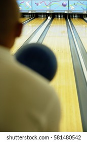 Man bowling, over the shoulder view