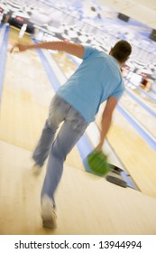 Man bowling, rear view (blurred motion)