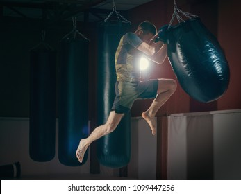 Man Boxer With with punching bag in gym. The guy trains fighter knee kick.