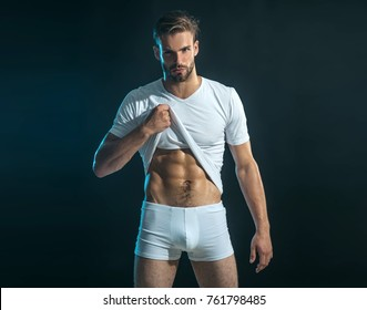 Man in boxer shorts shows his abdominal muscles, raising his t-shirt with his hand. Muscular sexy young man in white t-shirt