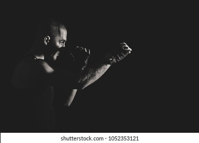The man in boxing gloves. Young Boxer fighter over black background. Boxing man ready to fight. Boxing, workout, muscle, strength, power - the concept of strength training and boxing. Black and white