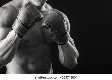 The man in boxing gloves. Young Boxer fighter over black background. Boxing man ready to fight. Boxing, workout, muscle, strength, power - the concept of strength training and boxing