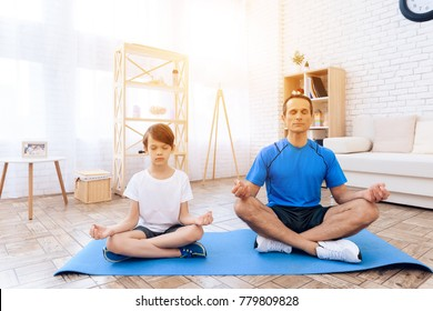 The man and the boy are engaged in yoga. This is father and son. They are at home. They meditate.