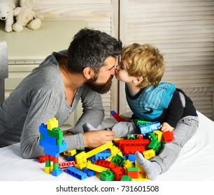 Man and boy play together on wooden wall background. Son kisses father in his nose, making colorful toy bricks constructions. Family and childhood concept. Dad and kid build of plastic blocks