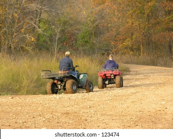 Man and boy riding all terrain vechicles.