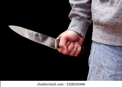 Man brandishing kitchen knife in a threatening manner. Isolated on black.