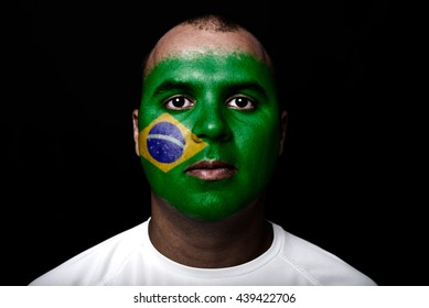 Man with Brasil flag painted on  his face on black background