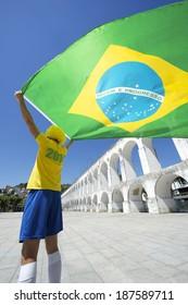 Man in Brazil colors 2014 shirt waving Brazilian flag over Arcos da Lapa Arches blue sky Rio de Janeiro Brazil