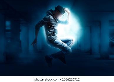 Man break dancing on dark light background