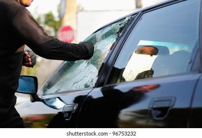 man breaking car window