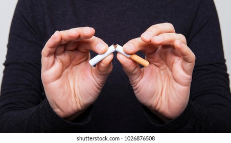Man is breaking cigarette and giving advice to stop smoking.