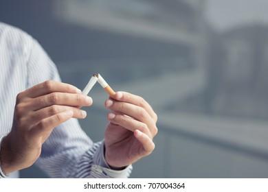 Man breaking cigarette in half. Stop smoking concept.