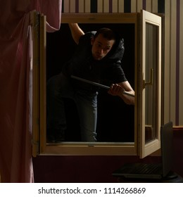 Man breaking-in the house through the window
