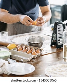 A man breaks an egg and pours the yolk into a metal dish. Cooking at home.