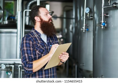 man at brewery taking notes on brewing process