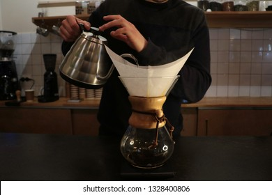 A man brews coffee, in the hands of Kemeks and a kettle. Barista works in a cafe. Coffee house. Boy barista. one of the step of making fantastic coffee. chemex