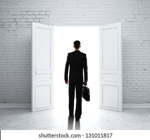 man in brick room with open door