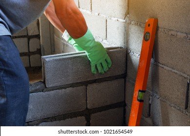 man bricklayer is catch cement brick block for To get straight In the wall construction.