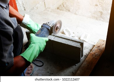 man bricklayer is cutting cement brick block with Small cutter machine for wall construction in new home
