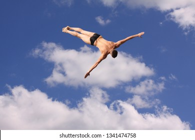 Man in brief swimsuit flying in the sky with white clouds below him - Photomanipulation - Image
