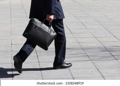 Man with briefcase walking on the street, person in a business suit rushing to a meeting. Concept of businessman, official, politician, career advancement, quarry growth, social climber