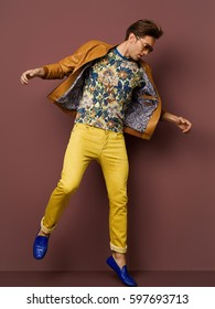 Man to bright clothes, a t-shirt with a bright print, yellow jeans, an orange jacket, dark glasses costs on a brown background