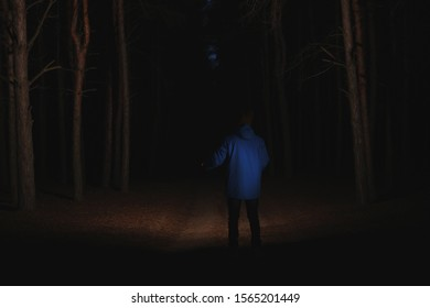Man with bright flashlight in forest at night