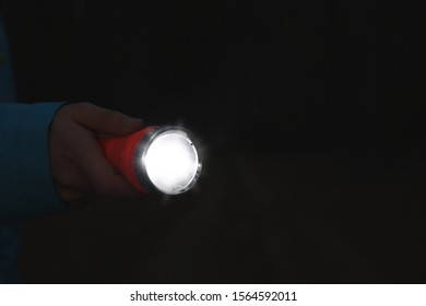 Man with bright flashlight at night, closeup. Space for text