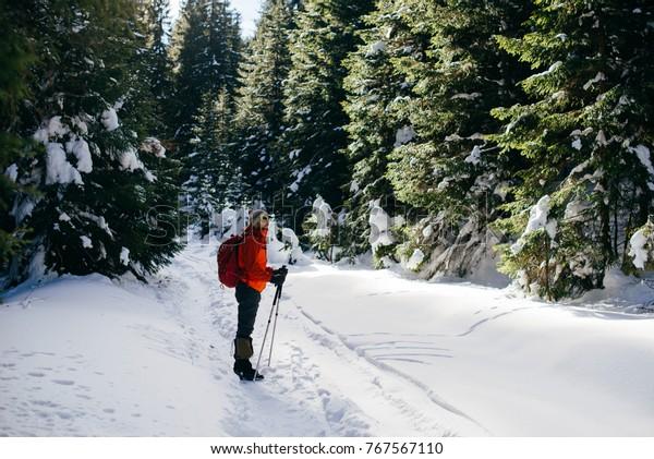 A man in bright sportswear trekking in a winter forest