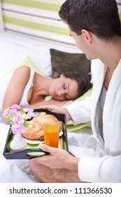 Man bringing the breakfast his girlfriend to in bed