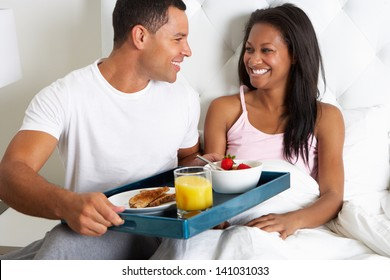 Man Bringing Woman Breakfast In Bed On Tray